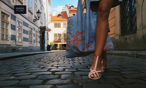 A women walking down a cobblestone path with a shopping bag
